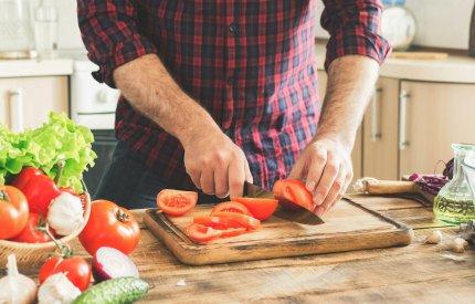image of food preparation - man chopping tomatoes