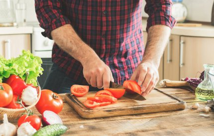 image of food preparation - man chopping tomatoes
