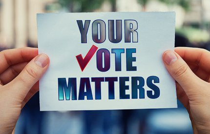 Person holding a card that reads your vote matters